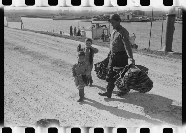 Spanish trapper and his children taking muskrat pelts into the FSA (Farm Security Administration) auction sale which is held in a dancehall on Delacroix Island, Louisiana. The fur buyers come from New Orleans. See general caption no. 1