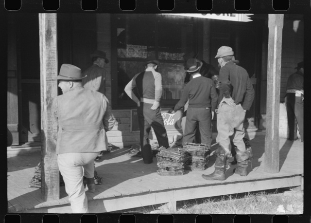 Spanish trappers and fur buyers waiting around while muskrats are being graded during auction sale on porch of community store, St. Bernard, Louisiana