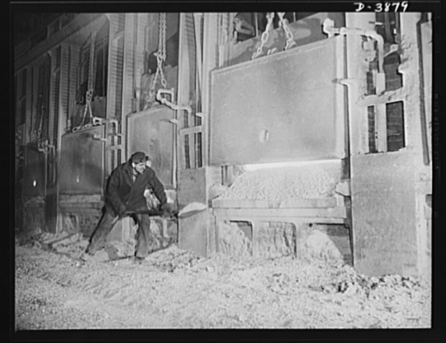Steel production. A step in the making of steel. A workman at an Eastern steel plant banks the doors of an open hearth furnace after the charge of steel