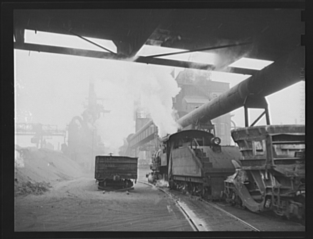 Steel production. Iron for our war machine. A busy blast furnace and the boiler house of another furnace are the background for a train of cinder ladles. Republic, Youngstown
