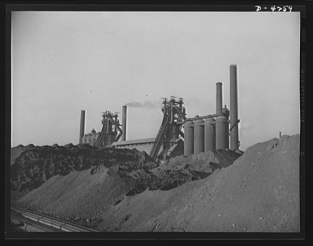 Steel production. Iron for the sinews of war. Huge ore piles feed the hungry maws of the blast furnaces. From the iron here produced will be made the various steels required by our armed forces. Carnegie-Illinois Steel Corporation. Farrell, Pennsylvania
