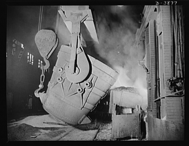 Steel production. Molten steel for war industries. A ladle of molten iron is poured into an opne hearth furnace for coversion into steel. Note safety latch on the crane hook. Republic, Youngstown
