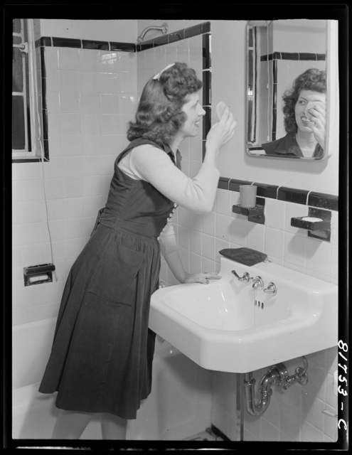 Stenographer has the use of a tiled bathroom in which to powder her nose and wash while she works for the Foreign Function Bureau, which is housed in a converted apartment building. Washington, D.C.