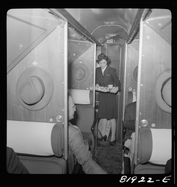 Stewardess serving dinner aboard an American airliner enroute from Washington to Los Angeles