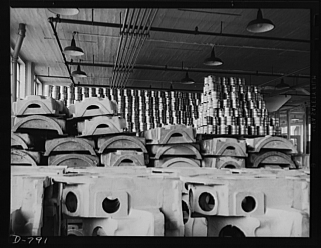 Storage of rough stock at the Packard marine engine plant, Detroit, Michigan. Photo shows, in foreground, the upper and lower halves of aluminum crankcases. Stacked in the background are stainless steel cylinder water jackets