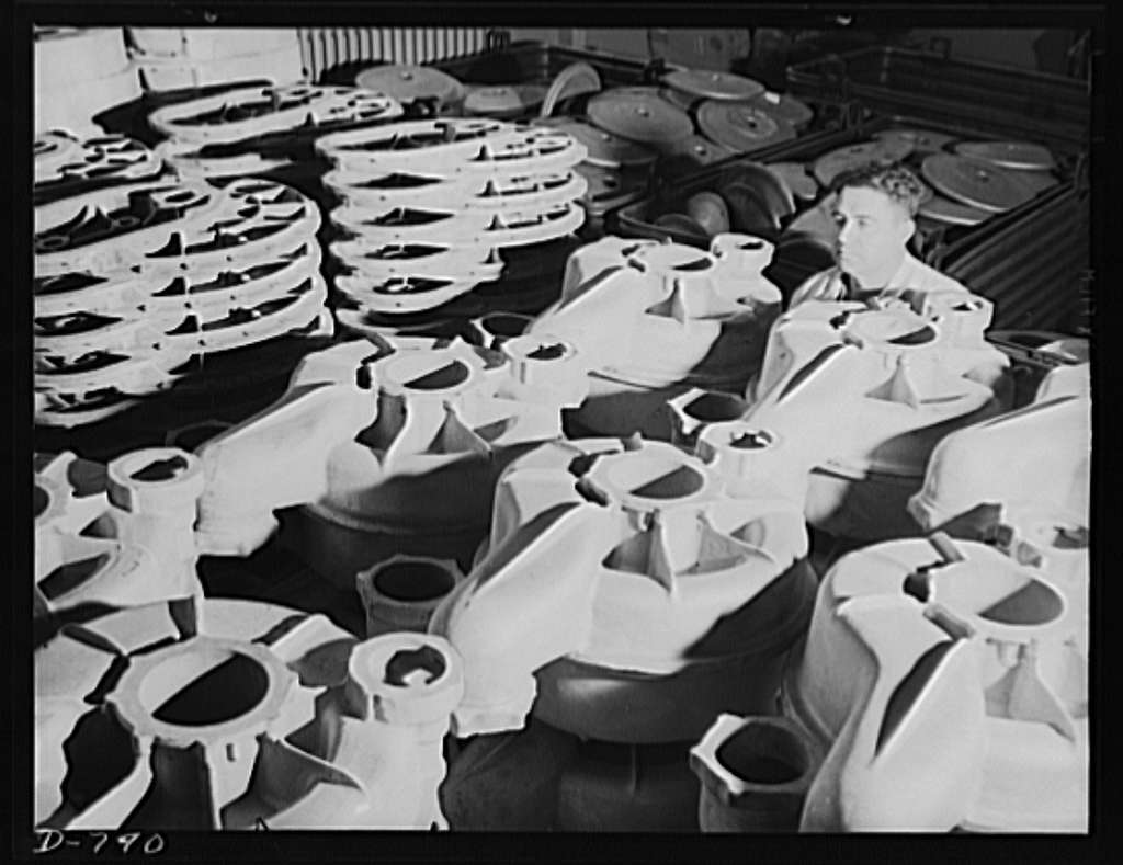 Storage of rough stock at the Packard marine engine plant, Detroit, Michigan. Photo shows, in foreground, super-charger impeller casings. In the left background are large aluminum super-charger gear housing. The right background shows a pile of steel reverse gear crankshaft flanges