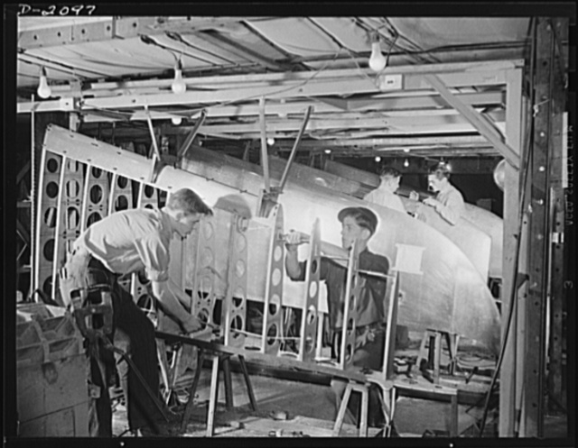Subcontracting aircraft parts. Here is one of the airplane sub-assembly production lines at an Ohio plant, which was a former airship dock. These are control surfaces for military aircraft, being assembled here for shipment to plane plants. Goodyear, Akron, Ohio