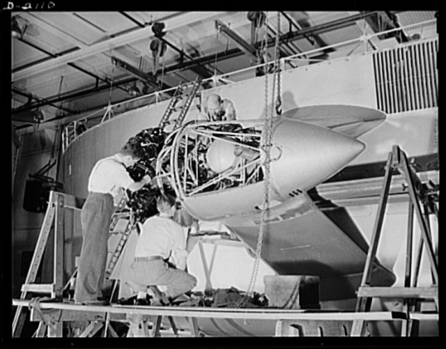 Subcontracting aircraft parts. Nearly ready to take its place in the battle for humanity, this control car for a naval non-rigid airship is receiving the finishing touches at the huge airship dock of an Ohio rubber company. Workers are here installing one of the two powerful motors which provide the power for the ship. Goodyear, Akron, Ohio