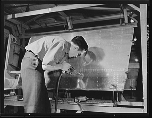 Subcontracting aircraft parts. This riveter is applying the finishing touches to highly-polished surface of a portion of aircraft sub-assembly at an Ohio plant. Goodyear, Akron, Ohio