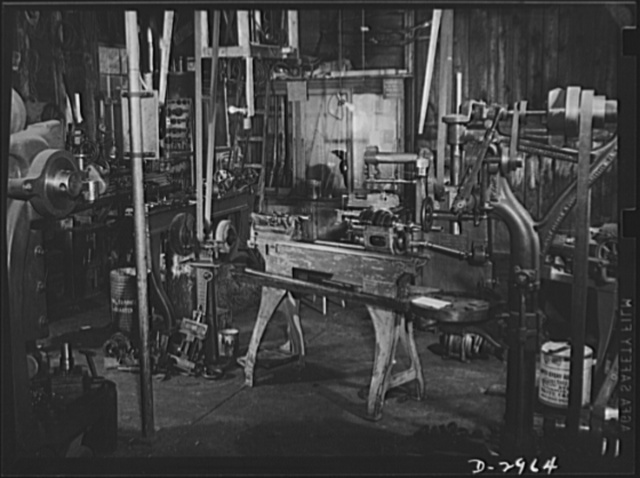 Subcontracting (Beery and Sons). Plant conversion means machine conversion. This lathe at the Beery and Sons shop in Harrisonburg, Virginia, is being fitted for production of a small part needed by a war contractor. To the left of the lathe are some of the hurriedly constructed jigs and chucks turned out at the shop to speed delivery of various bits and pieces, often cutting the schedule as high as ninety-percent