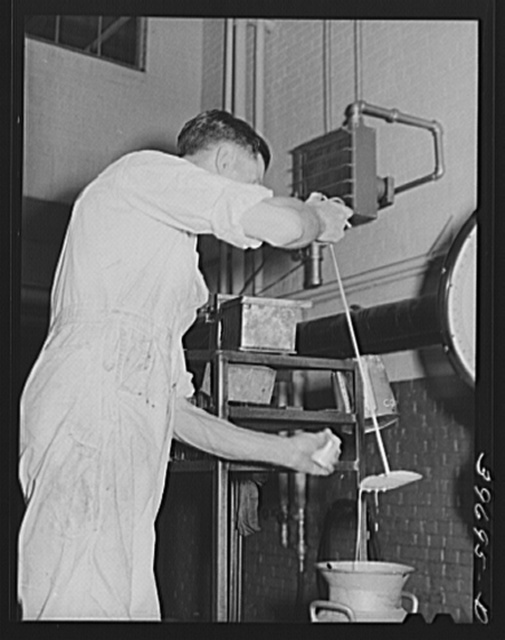 Taking a sample of milk to determine butter fat content. Dairymen's Cooperative Creamery. Caldwell, Canyon County, Idaho