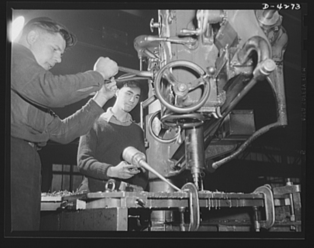 Tank armor production. Carnegie-Illinois Steel Corporation. Farrell, Pennsylvania. Rivet holes for the armor plates of military tanks are run on a vertical drill press in an Eastern mill
