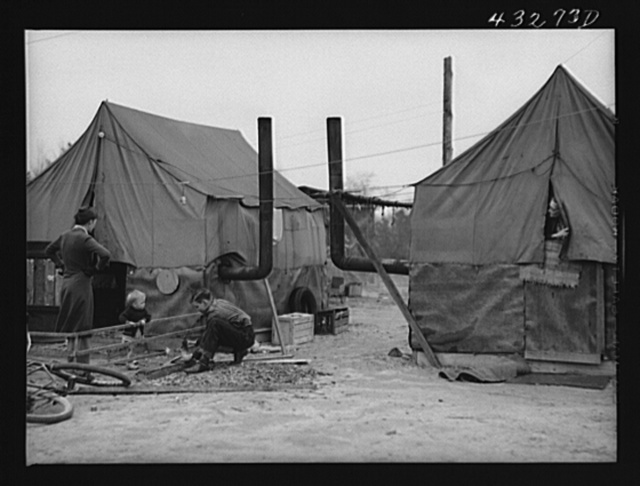 Tent of migratory workers employed at Fort Bragg, North Carolina. These tents were part of a small settlement at Manchester, North Carolina (about twelve miles from Fayetteville). They were paying a dollar a week for tent space-- this included water and light. One spigot at the general store furnished water for the entire camp up to 6 p.m.