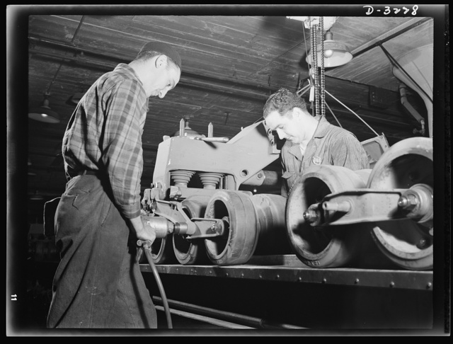 The bogy assembly of an Army halftrac scout car plays an important part in a very capable vehicle. It requires skilled workers on the production line of a large Midwest truck plant. White Motor Company, Cleveland, Ohio