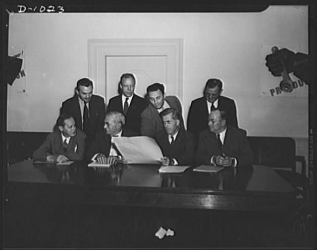 The first meeting of the Supply Priorities and Allocations Board, Washington, D.C., September 2, 1941. Seated left to right: Harry L. Hopkins, Special Assistant to the President, supervising lend-lease Program; William S. Knudsen, Director-General of the Office of Production Management (OPM); Henry A. Wallace, Vice President of the United States, and Chairman of the Board; Donald M. Nelson, Executive Director of the Board and Director of the Priorities Division, OPM. Standing, left to right: James V. Forrestal, Undersecretary of the Navy (who was present in place of Secretary Frank Knox, out of town on this day and unable to be present); Robert P. Patterson, Undersecretary of War (sitting in for Secretary of War Stimson, who was unable to attend); Leon Henderson, Administrator, Office of Price Administration (OPA) and Director of the Civilian Supply Division, OPMt; Sidney Hillman, Associate-Director of Labor Division, OPM