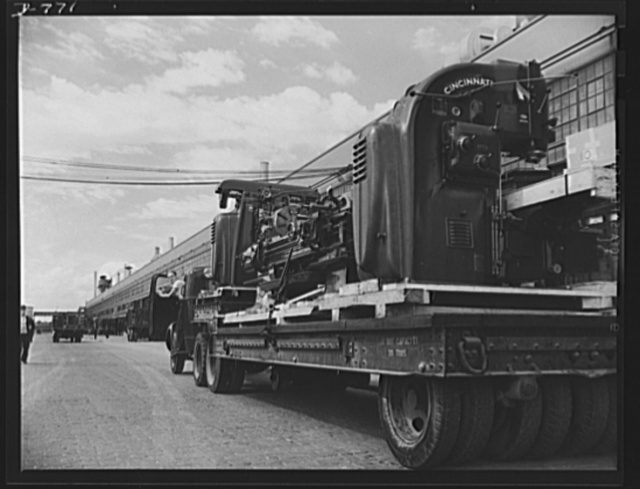 The Ford Motor Company has constructed and equipped, in eight months an airplane engine building. It covers 17.8 acres, will employ over 14,000 men, will turn out Pratt and Whitney engines at the rate of one an hour for sixteen hours a day. Building and machinery cost twenty-three million dollars. Photo shows three machines on truck, on their way to be installed in the new aircraft building