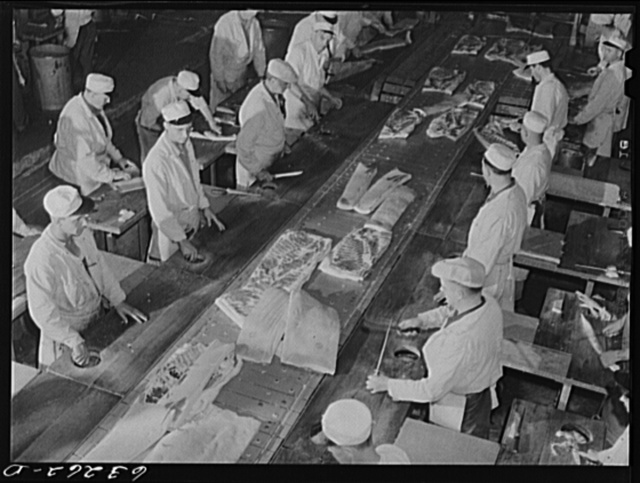 The hog cut: hogs come chilled and split, and go through the crew of butchers on a moving belt. Packing plant. Austin, Minnesota