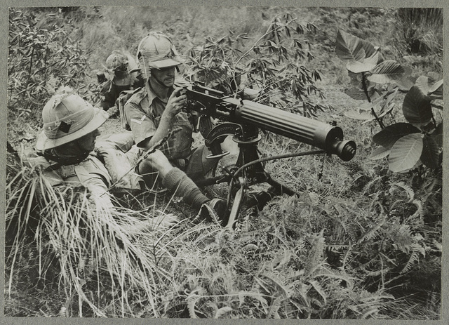 The Manchesters in the Far East A battalion of the Manchester Regiment in the Far East is busily engaged in preparing for anything the future may have in store and the art of camouflage is not being overlooked. Photo shows - a Vickers gun in use during an exercise.