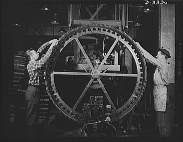 """The tracks for an Army halftrac scout car begins to take shape on the """"building wheel"""" of a Midwest tire plant. Goodrich, Akron, Ohio"""