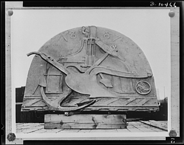 This plaque, bearing a design showing a plow, anchor and steam hammer, symbolizing the agriculture, commerce and manufacturing of the east, is being disposed of as scrap to aid the war effort. The Union Pacific Railroad has notified the Industrial Salvage Section of the War Production Board (WPB) Bureau of Industrial Conservation. It was erected on the road's Missouri River Bridge in 1888. The weight of the plaque is estimated at 1000 pounds of bronze and steel, including frame supports. It is five feet high, six feet wide and four inches thick