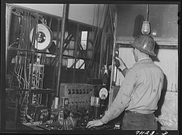 This workman controls amounts of materials going into concrete used in construction of Shasta Dam. Shasta County, California