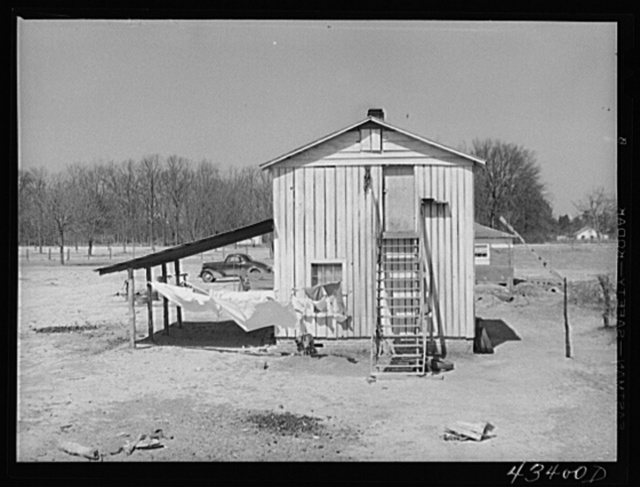 Tobacco barn converted into living quarters for families of workers from Fort Bragg. Near Fayetteville, North Carolina