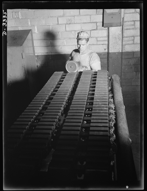 Tracks for Army vehicles, fresh from the curing press of a large Ohio tire plant. Grooves are buffed on the ends of the track section. Goodrich, Akron, Ohio