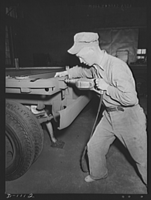 Trailers for defense transportation. Winter Weiss Company, Denver, Colorado. Manufacture of semi-trailers for Defense transportation. These trailers are eqipped with a combination platform stake body and are intended for general use in Army camps and depots. They carry a payload of 7,000 pounds. This worker is attaching reflectors to the rear of the trailer frame