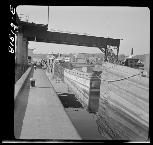 Tug pulling barges through Lock Eleven. Erie Canal, New York