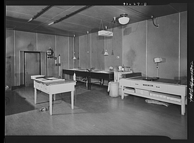 U.S. FSA (Farm Security Administration), later U.S. Office of War Information, photograph laboratory in the Auditor's Building. Washington, D.C. Enlarging room, showing a Leitz miniature enlarger and developing sinks