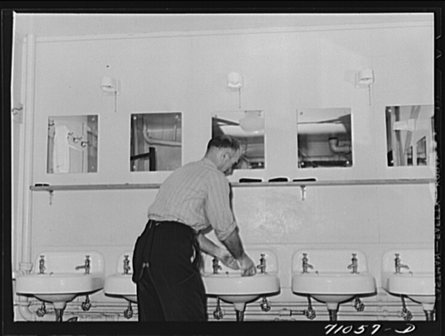 Vallejo, California. Workman at Mare Island shipbuilding yards in bathroom of FSA (Farm Security Administration) dormitory