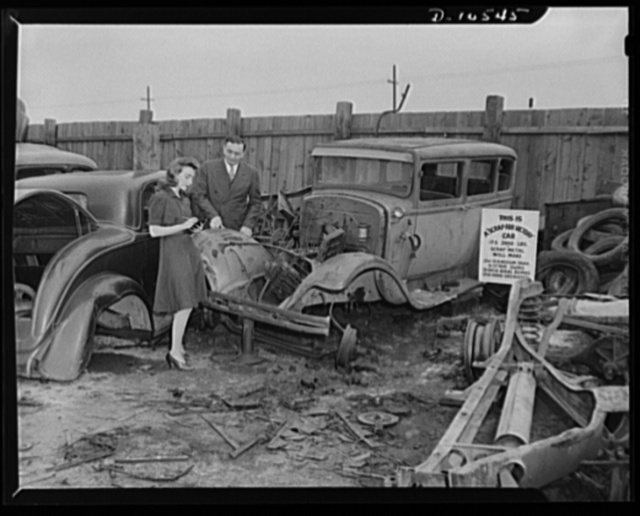 War Board launches auto graveyard program. W.F. Breuer, regional representative of the Auto Salvage Section, War Production Board, starts preliminary survey of jaloppies available for war production use. Miss Jane McCullough of the WPB local office takes notes