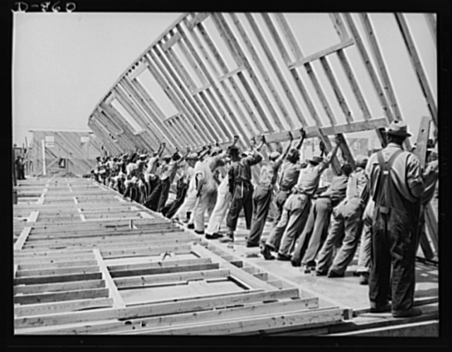 War Housing, Erie, Pennsylvania. The entire framework, including sections for doors and windows, is fabricated horizontally. The crew working here will later move to another site and repeat the procedure. This circulation of crews who are experienced in one type of construction adds to the speed with which defense homes are being built. Two crews of forty men each are used to raise the stud frames of a four-unit defense home. On the project shown here, one crew started the framework at 8:30am, fabricating it horizontally, and finished it at noon. The other crew moved in shortly after, erected the stud frame, ends, and floor joists, and finished the entire framework by 4:30pm the same day