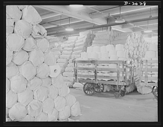 Warehouse view of cord stock. Cord stock as it is received from the mill. This special twist cotton cord comes from southern mills. It differs from other tire cords in that it is woven and twisted by gear-driven machinery instead of belt-driven equipment. Slips and strains of belt-machinery are reflected in the cord and on into the finished tire, whereas in a gear-driven machine there are no slippages, therefore no weakened cords in the finished tire. Firestone (General Tires), Akron, Ohio