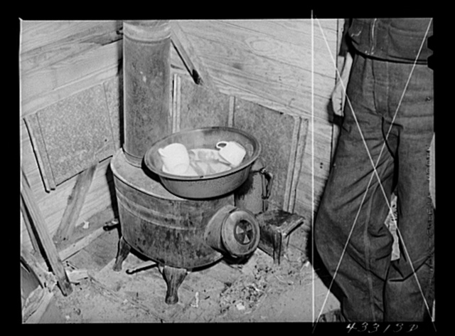 Washing dishes in a shack occupied by workers from Fort Bragg, North Carolina. Near Fayetteville