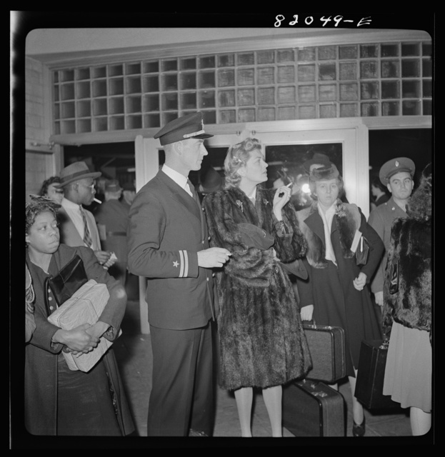 Washington, D.C. Christmas rush in the Greyhound bus terminal. Naval officer and his wife