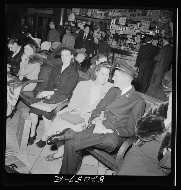 Washington, D.C. Christmas rush in the Greyhound bus terminal. Young lady and Naval officer