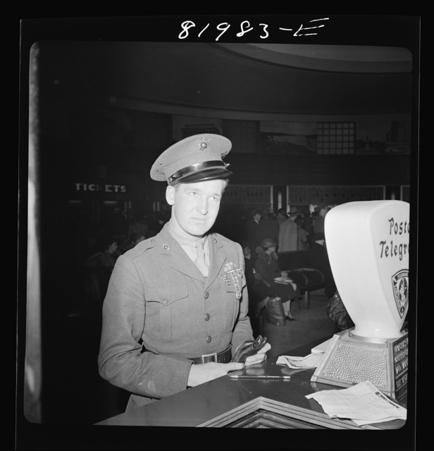 Washington, D.C.  United States Marine in Greyhound bus depot, just home from Cuba, thinking up a Christmas telegram to his folks at home