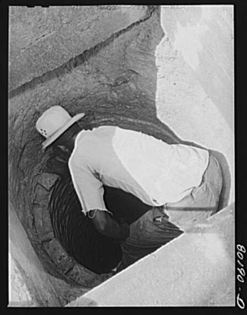 Well worker balances on siding of brick, removing them one at a time to the depth of ten feet, where the bricks will form a base for the cement cap. John Hardesty well project, Charles County, Maryland