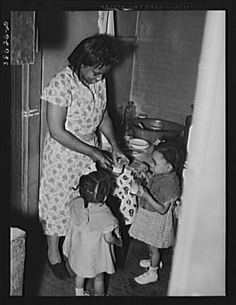 Wife of railroad worker feeding her children. Chicago, Illinois