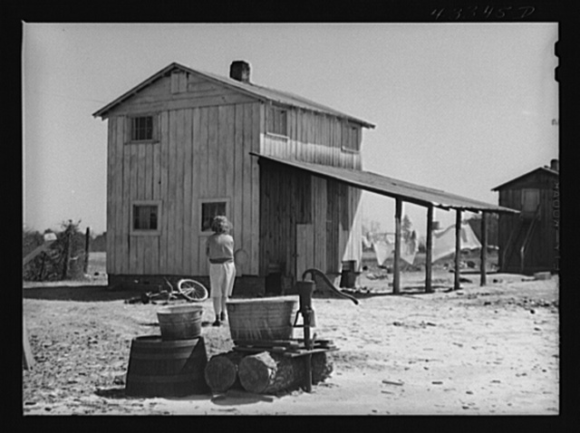 Woman fetching water. She lives with her family in lower part of the tobacco barn. Husband works at Fort Bragg. Near Fayetteville, North Carolina
