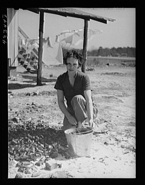 Woman who lives with her family in the upper part of tobacco barn, gathering coal. Husband works at Fort Bragg. Near Fayetteville, North Carolina
