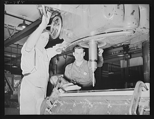 Workmen counter-boring stud holes for the cylinder barrel in an aluminum crank-case for the Packard marine engine. Packard marine engine plant, Detroit