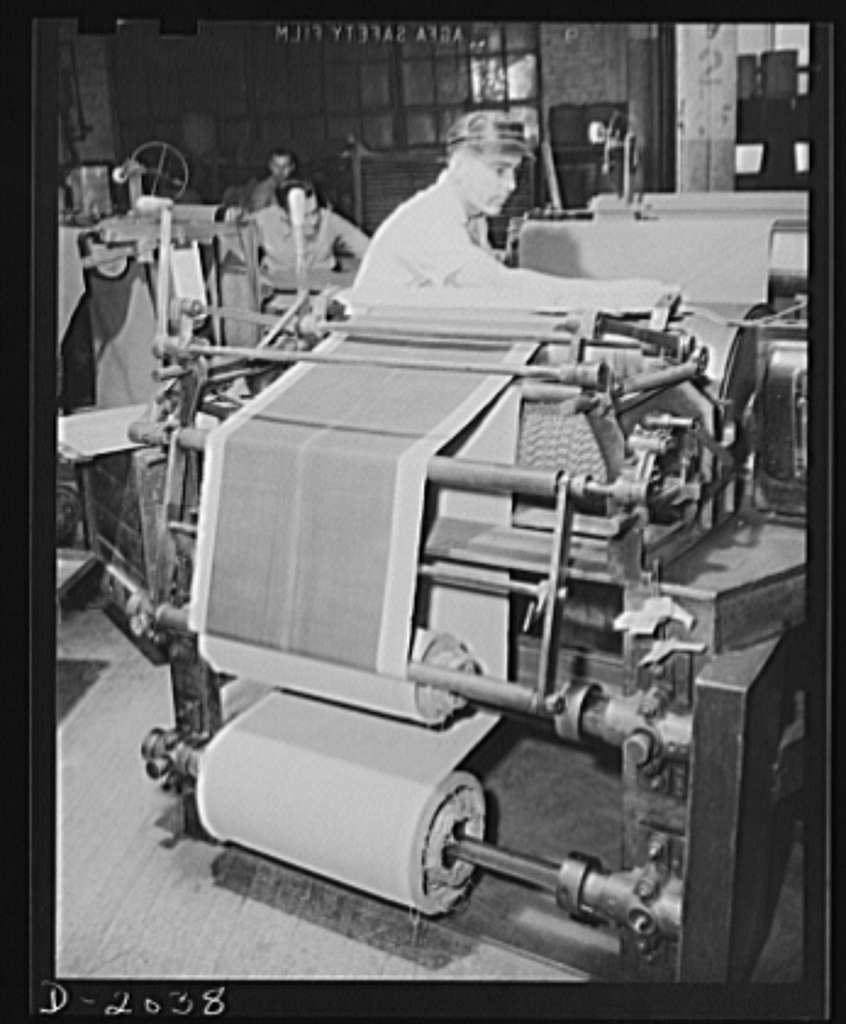 Wrapping in cloth prevents sticking. Reels of fabric may be stored for a few moments or a few days, wrapped in cloth to prevent it from sticking to itself when rolled up. These reels are brought from storage to machines such as this, in which the fabric is out on a powered bias cutter to exact length for one ply of a tire. This worker is making a layer of two plies, with the cords running at right angles, one laid on top of the other. This layer will later be used by a tire builder in building up the plies of his tire to the required number. Firestone (General Tires), Akron, Ohio