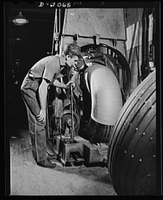 Wrapping truck tires. All sizes of tires can be wrapped by this machinery, which has an opening just large enough for the tire to pass through. It throws a semi-circular catapult through the middle of the tire; the catapult carries the roll of paper with it, unwinding as it goes. Firestone (General) Tires, Akron, Ohio