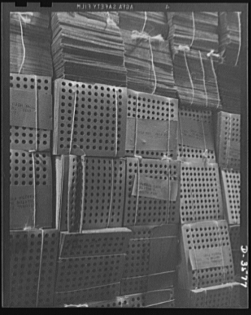 A converted cash register factory now producing war goods in enormous volume must keep on hand huge stocks of packing materials. These corrugated board inserts are made from waste paper and are used for packing shell parts. National Cash Register Company, Dayton, Ohio