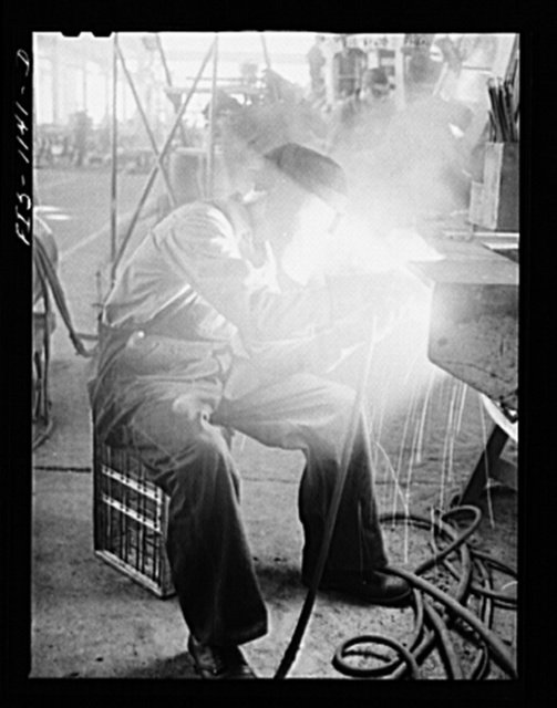 A defense worker who was born in Sweden, welding at a plant in Minnesota, possibly the Northern Pump Company in Minneapolis