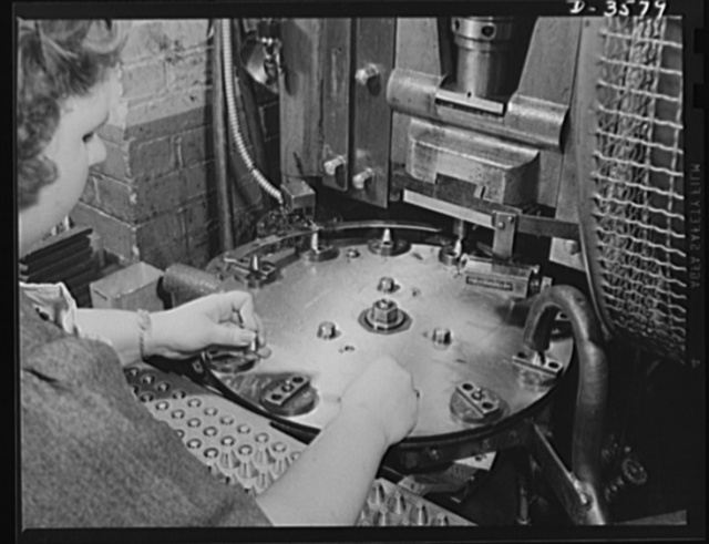 A dial feed press crimps 20mm fuses in a large plant which quickly changed over to the production of essential supplies for our armed forces. National Cash Register Company, Dayton, Ohio