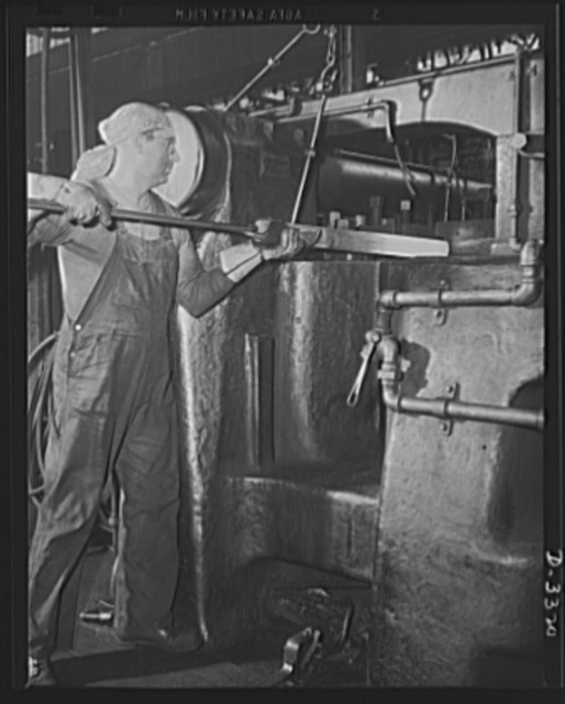 A husky upsetter and a forge that was turning out automobile parts a short time ago is one of the many combinations of skilled worker and efficient machine that keep the shells pouring in a steady stream from a converted auto plant. Oldsmobile, Lansing, Michigan