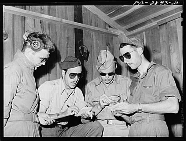"""A lieutenant of a """"Flying Sergeant"""" intercepter squadron (second from the left) charts the manner of the formations. Lake Muroc, California"""